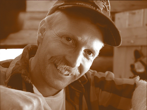Portrait of artist Jeff Fleming carving in his studio