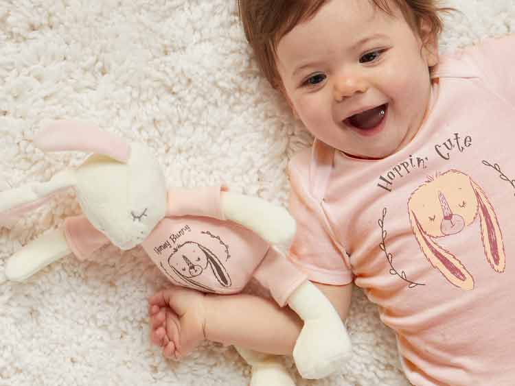 baby and stuffed animal in matching pink bunny hopping cute pajamas