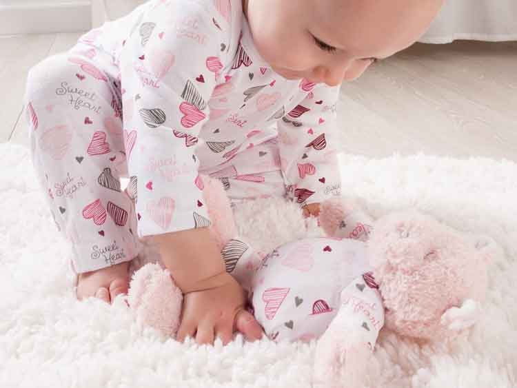 baby and stuffed animal in matching pink heart pajamas