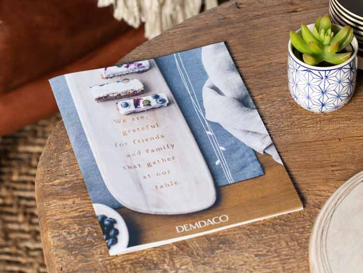 DEMDACO paper catalog lying on a wooden coffee table next to a plant