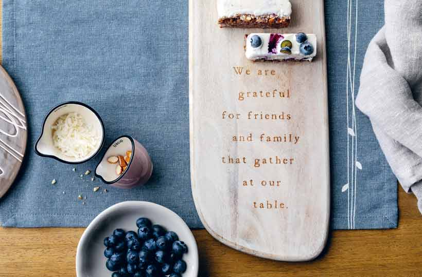 Wood serving board with the engraved words We are grateful for friends and family that gather at our table