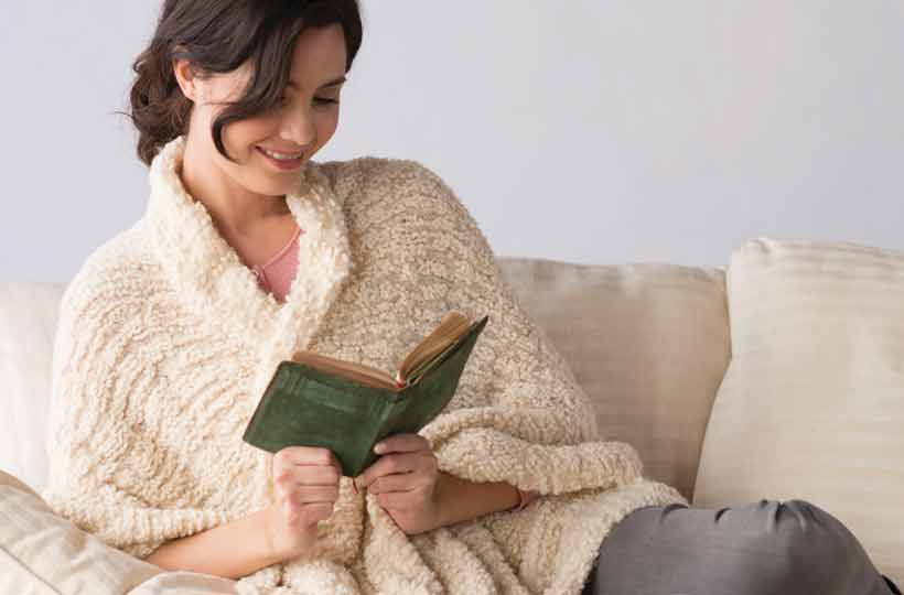 Woman wrapped in soft, cream shawl sitting on a couch reading a book