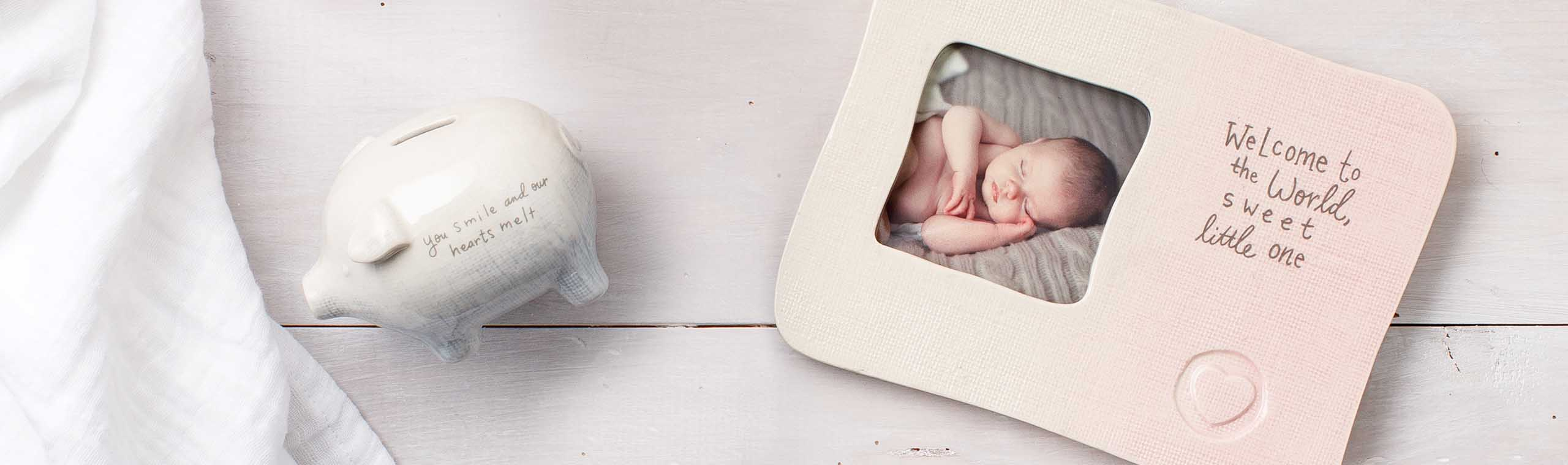White piggy bank and white and pink picture frame with baby picture