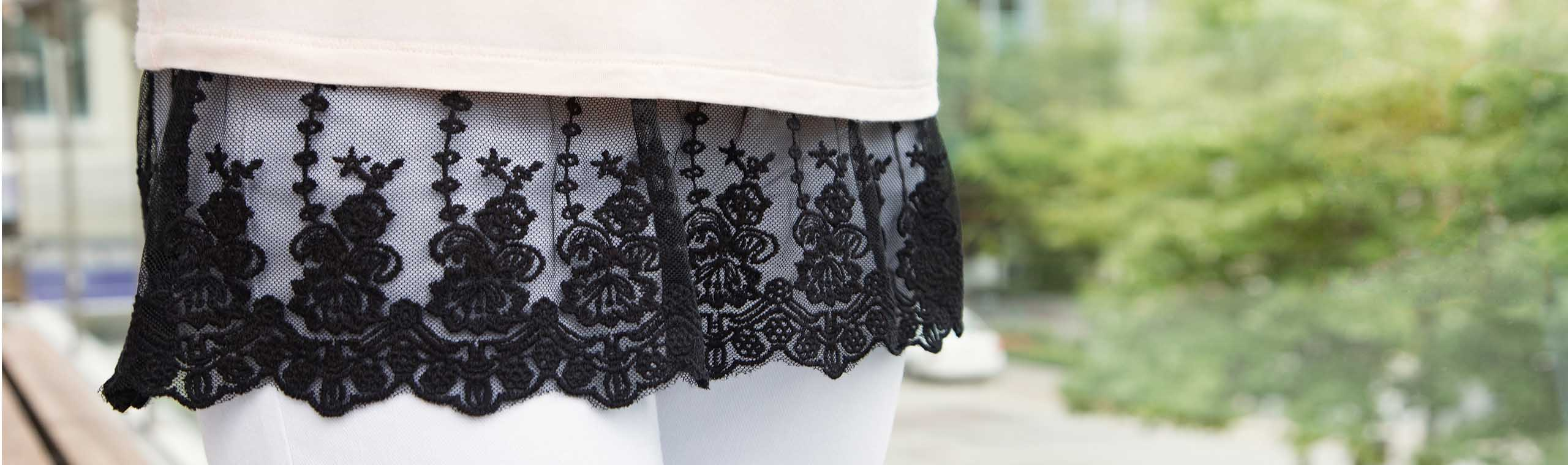 Woman wearing shirt with black lace along bottom edge