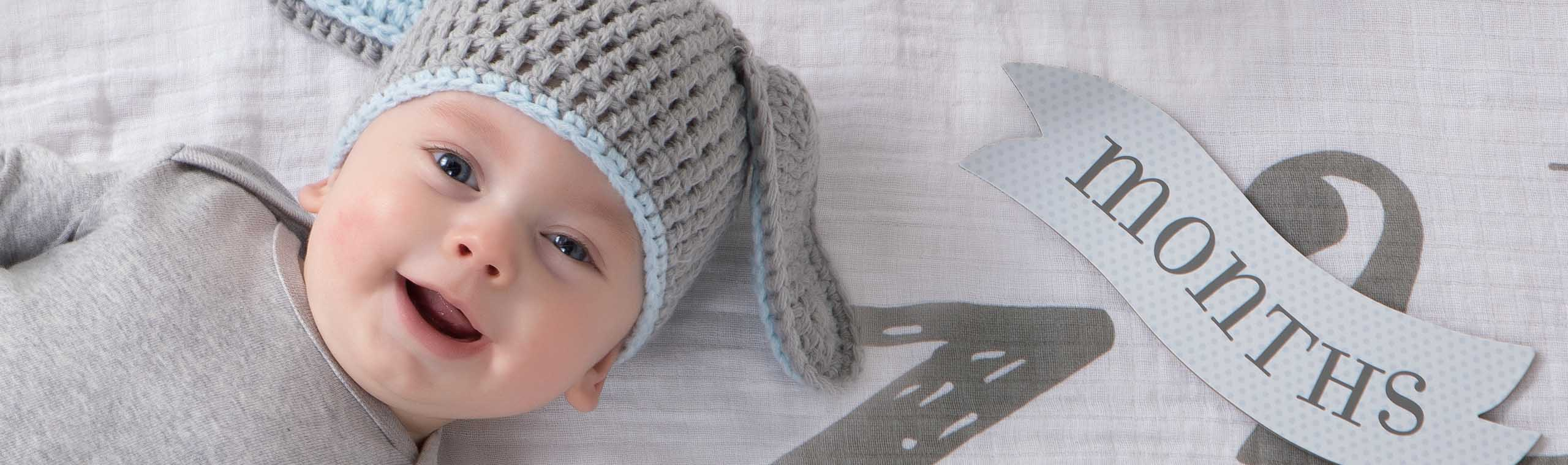 Baby lying on soft white and blue blanket wearing a knit gray and blue hat