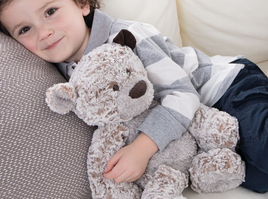boy on couch holding a giving bear